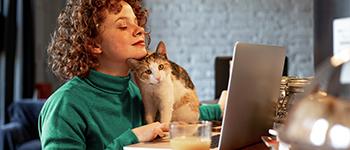 vrouw die thuis werkt met kat op schoot