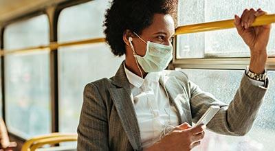 afbeelding van vrouw in de bus met mondkapje