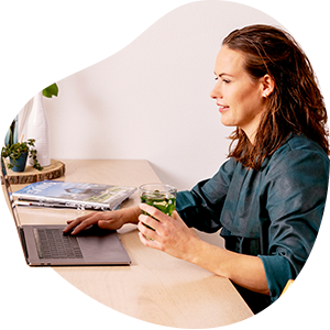 De afbeelding toont een jonge vrouw die op een laptop kijkt.