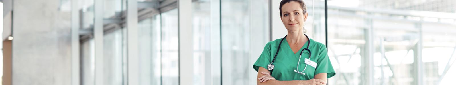 Vrouwelijke arts met stethoscoop om haar hals staat in de gang van een ziekenhuis
