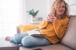 Jonge vrouw zit ontspannen op de bank met een kop thee