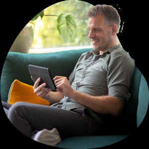 Man leest op zijn tablet de voorwaarden van zijn zorgverzekering.