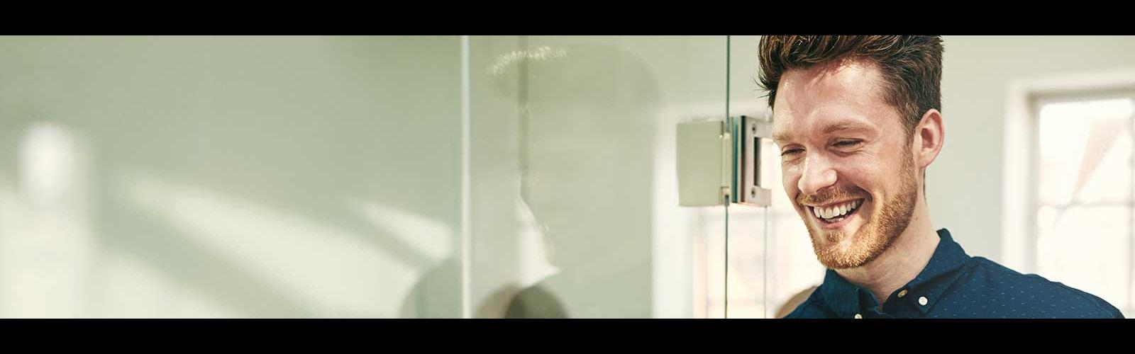 Jongen met baard en blauw shirt op kantoor