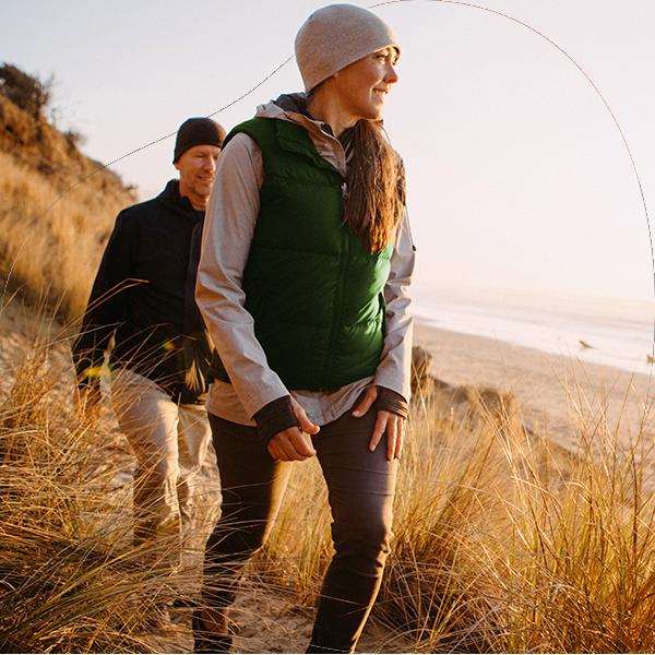 Man en vrouw aan het hiken langs de kust