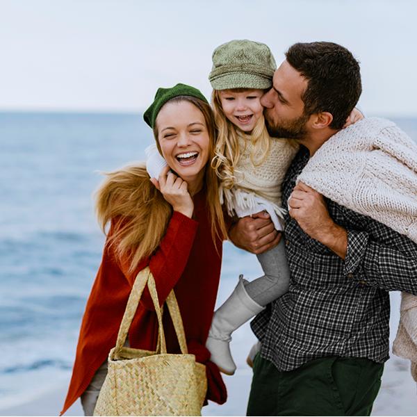 Moeder, vader en kind op het strand knuffelen elkaar
