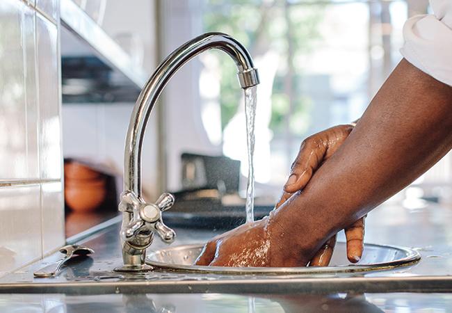 Verpleegkundige wast handen onder de kraan