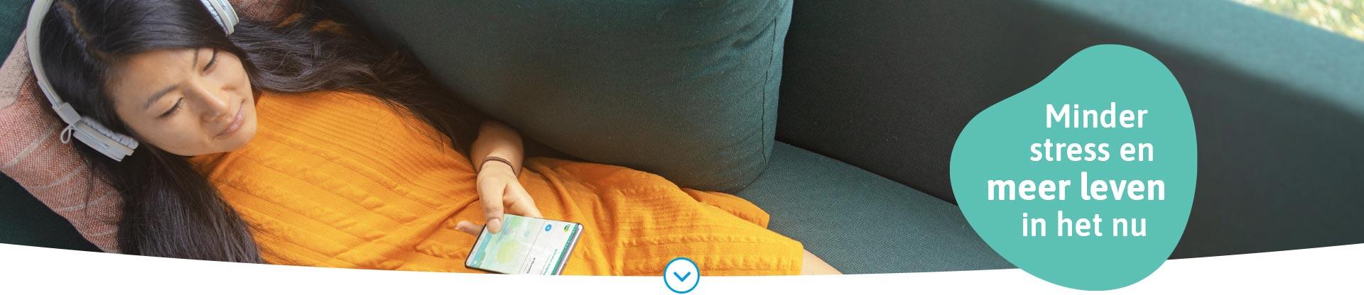 Afbeelding van een ontspannen vrouw die gebruikmaakt van de VGZ Mindfulness coach app via haar telefoon