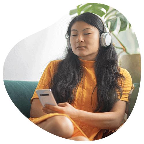 Vrouw die met een headset op luistert naar een mindfulness oefening op haar telefoon