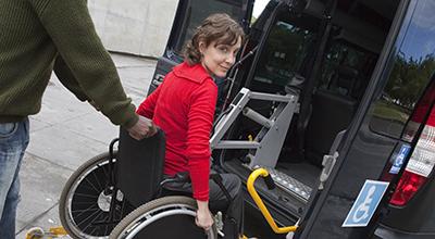 Vrouw in rolstoel wordt vervoerd met taxi