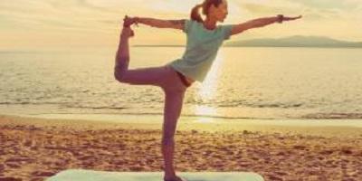 Op de afbeelding een vrouw op het strand die yoga doet.
