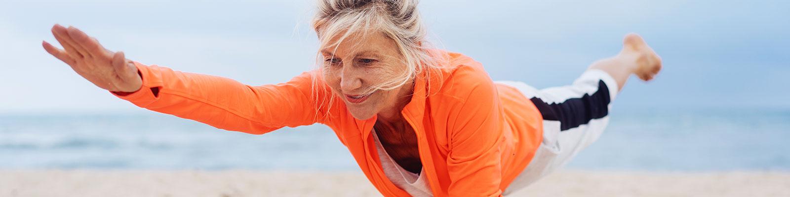 Oudere vrouw met rode jas doet yoga in de buitenlucht