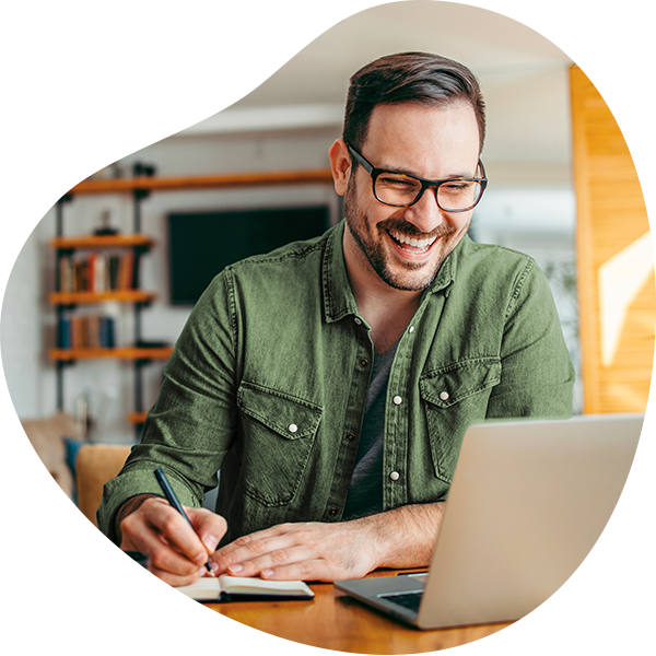 Lachende man met groen shirt achter laptop