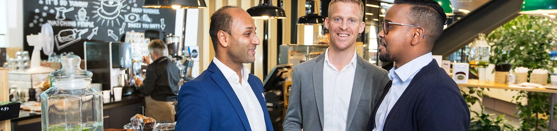 Drie mannelijke collega's in gesprek in bedrijfsrestaurant