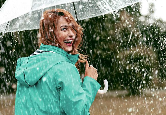 Lachende vrouw met paraplu in de regen