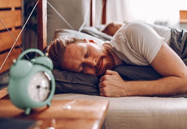 Man ligt te slapen in bed met een wekker naast hem op het nachtkastje