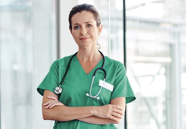 Vrouwelijke arts met groene kleding en stethoscoop om de hals