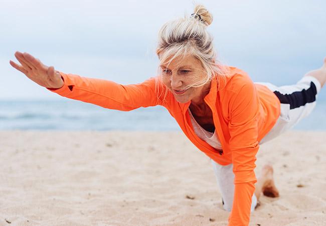 Oudere vrouw doet yoga op het strand