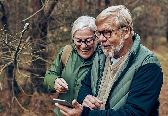 Twee senioren wandelen in het bos
