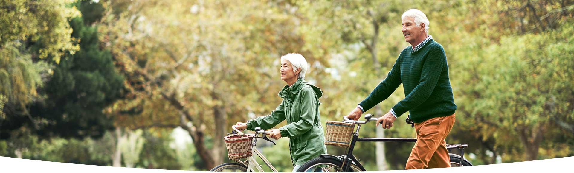 Oudere man en vrouw wandelen met fiets aan de hand