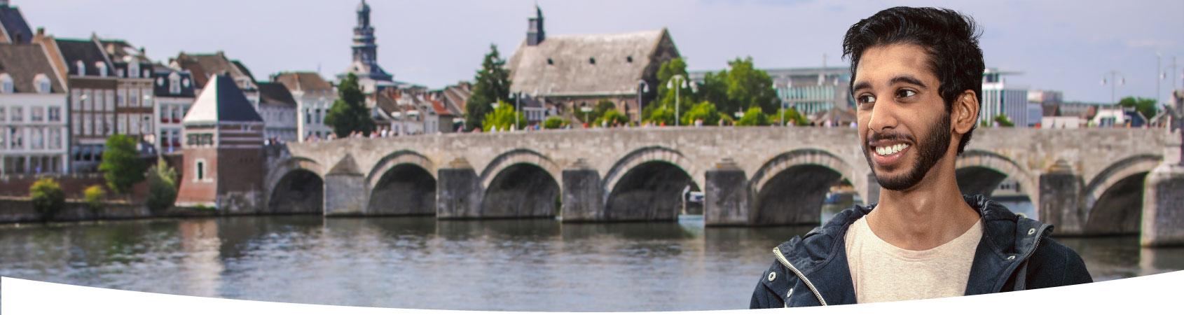 Jongen staat vlakbij rivier de Maas in Maastricht